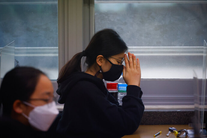 A student  wearing a face mask prays before the start of the annual college entrance examination amid the coronavirus pandemic at an exam hall in Seoul, South Korea, Thursday, Dec. 3, 2020. South Korean officials are urging people to remain at home if possible and cancel gatherings as about half a million students prepare for a crucial national college exam. (Kim Hong-Ji/Pool Photo via AP)