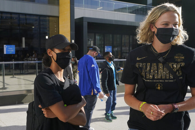 Stanford basketball players Anna Wilson, left, and Alyssa Jerome are interviewed as they arrive at Chase Center before an NBA basketball game between the Golden State Warriors and the Utah Jazz in San Francisco, Monday, May 10, 2021. (AP Photo/Jeff Chiu)