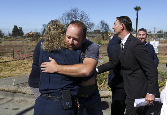 Brad Sherwood, center, hugs Rincon Valley and Windsor fire prevention officer Cyndi Foreman on his property where his home was destroyed in October 2017 by wildfires, in Santa Rosa, Calif., Wednesday, July 11, 2018. Victims of California's deadliest wildfires and local politicians are calling on state lawmakers to stop trying to overhaul the state's liability laws on wildfires. (AP Photo/ Lorin Eleni Gill)