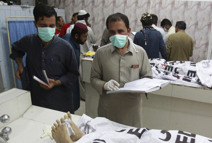 Pakistan hospital staff collect information of alleged terrorists killed by security forces, at mortuary in Quetta, Pakistan, Thursday, May 16, 2019. Pakistani police say security forces acting on intelligence raided a militant hideout in the town of Mastung in southwestern Baluchistan province, triggering a shootout that killed many suspects. (AP Photo/Arshad Butt)