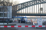 The excavator that uncovered the bomb stands in front of the Hohenzollern Bridge in Cologne, Germany, Tuesday, Jan. 21, 2020. A train station, an opera house and a TV station in the western Germany city of Cologne are evacuated on Tuesday as experts prepare to defuse an American 500-kilogram (1,100-pound) bomb from World War II. (Roberto Pfeil/dpa via AP)