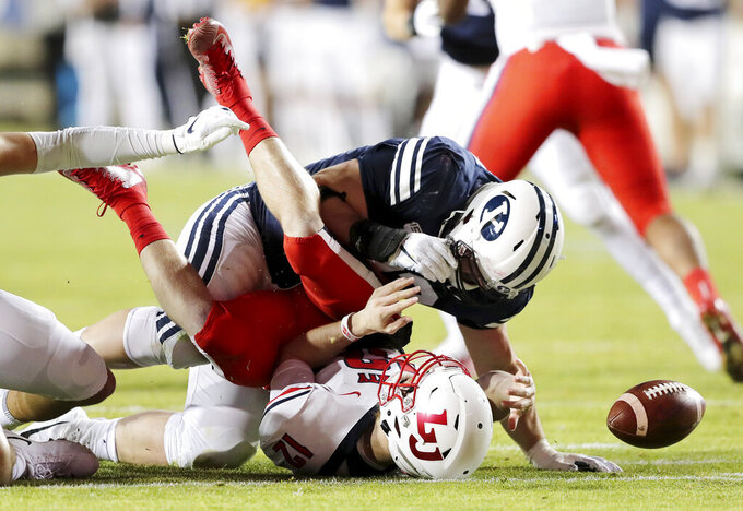 Liberty quarterback Stephen Calvert (12) loses the ball as he is hit by BYU defensive lineman Bracken El-Bakri (93) after being sacked by BYU linebacker Keenan Pili during an NCAA college football game in Provo, Utah, Saturday, Nov. 9, 2019. (Scott G. Winterton/The Deseret News via AP)
