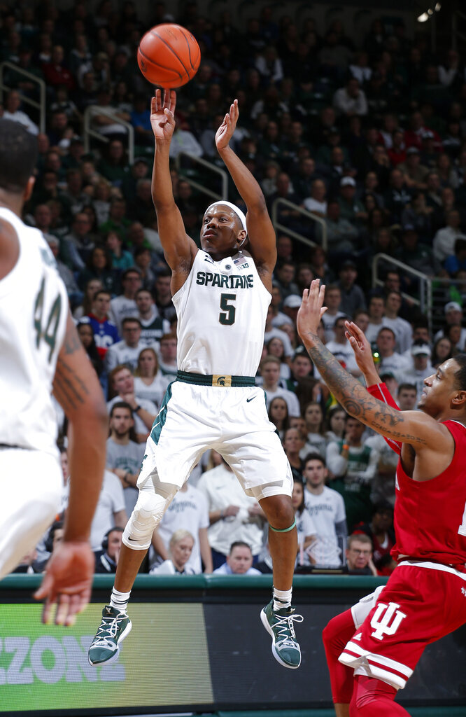 FILE - In this Feb. 2, 2019, file photo, Michigan State's Cassius Winston (5) shoots past Indiana's Devonte Green, right, during the second half of an NCAA college basketball game, in East Lansing, Mich. Winston has joined a select group of players in program history as an All-America player and Big Ten player of the year. If he can help the Spartans win two more games, he'll join Magic Johnson and Mateen Cleaves as the school's national championship-winning point guards. (AP Photo/Al Goldis, File)