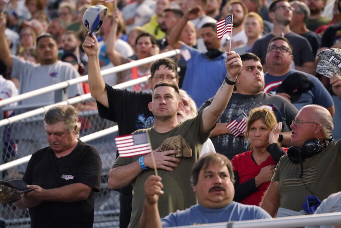 Race fans hold U.S. flags during the singing of the national anthem before the NASCAR Cup series auto race in Richmond, Va., Saturday, Sept. 11, 2021. (AP Photo/Steve Helber)