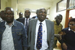 Former sports cabinet secretary Hassan Wario, second left with cap, former sports officials Haron Komen, right, who served as Director of Administration and Patrick Nkabu, left, appear in Milimani court, Nairobi, Kenya, Friday, Oct. 19, 2018. Kip Keino, one of seven Kenyan Olympic and government officials accused, denied wrongdoing in the Kenyan Olympic corruption scandal in an interview with The Associated Press and didn't appear in court as expected Friday as prosecutors consider withdrawing charges against him and making him a witness over the alleged misuse of more than $545,000. (AP Photo/Brian Inganga)