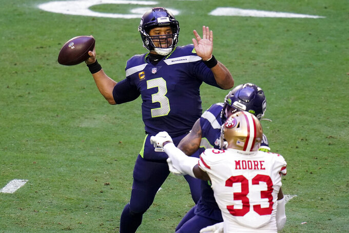Seattle Seahawks quarterback Russell Wilson (3) shows as San Francisco 49ers defensive back Tarvarius Moore (33) pursues during the first half of an NFL football game, Sunday, Jan. 3, 2021, in Glendale, Ariz. (AP Photo/Ross D. Franklin)