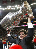 FILE - In this June 19, 2006, file photo, Carolina Hurricanes coach Peter Laviolette celebrates with the NHL hockey Stanley Cup after Game 7 of the finals against the Edmonton Oilers in Raleigh, N.C. The Washington Capitals hired Peter Laviolette, who won the Stanley Cup with the Carolina Hurricanes in 2006, as coach on Tuesday, Sept. 15, 2020. (Paul Chiasson/The Canadian Press via AP, File)