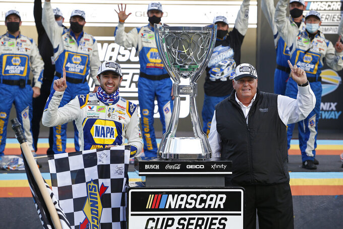 Chase Elliott, left, and car owner Rick Hendrick celebrate in Victory Lane following their season championship victory in the NASCAR Cup Series auto race at Phoenix Raceway, Sunday, Nov. 8, 2020, in Avondale, Ariz. (AP Photo/Ralph Freso)