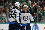 Winnipeg Jets center Mark Scheifele (55) and left wing Kyle Connor (81) celebrate a goal by Connor in the second period of an NHL hockey game against the Dallas Stars in Dallas, Thursday, Nov. 21, 2019. (AP Photo/Tony Gutierrez)