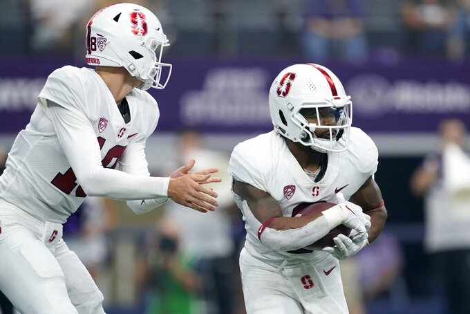 Stanford quarterback Tanner McKee hands the ball off to running back Nathaniel Peat in the first half of an NCAA college football game in Arlington, Texas, Saturday, Sept. 4, 2021. (AP Photo/Tony Gutierrez)