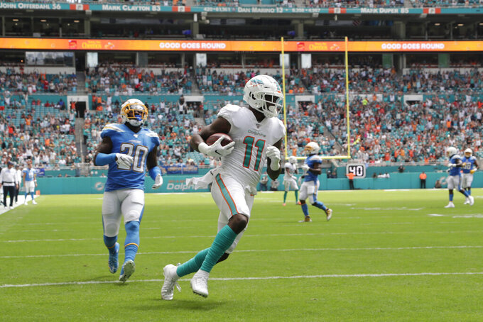 Miami Dolphins wide receiver DeVante Parker (11) runs for a touchdown ahead of Los Angeles Chargers defensive back Desmond King (20), during the first half at an NFL football game, Sunday, Sept. 29, 2019, in Miami Gardens, Fla. AP Photo/Lynne Sladky)