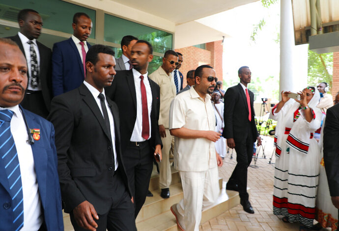 Ethiopia's prime minister Abiy Ahmed, center,  arrives in Khartoum, Sudan on Friday, June 7, 2019,  to try and mediate between the ruling military and the country's protest leaders amid an army crackdown that has killed over 100 people this week. Ahmed first met with Sudanese generals who in April ousted longtime autocrat Omar al-Bashir and took over the country after four months of mass protests against his rule. The protesters, however, remained in the streets, demanding the military hand over power to civilians.  (AP Photo)