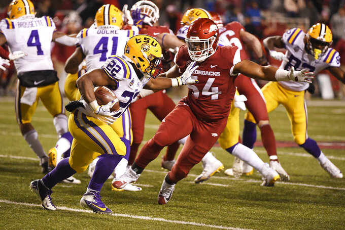 LSU running back Clyde Edwards-Helaire runs past Arkansas defender Terrell Collins during the second half of an NCAA college football game, Saturday, Nov. 10, 2018, in Fayetteville, Ark. LSU won, 24-17. (AP Photo/Michael Woods)