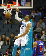 Charlotte Hornets' Miles Bridges (0) slaps down a dunk as Detroit Pistons' Bruce Brown (6) can only watch during the second half of an NBA preseason basketball game in Charlotte, N.C., Wednesday, Oct. 16, 2019. The Pistons won 116-110. (AP Photo/Bob Leverone)