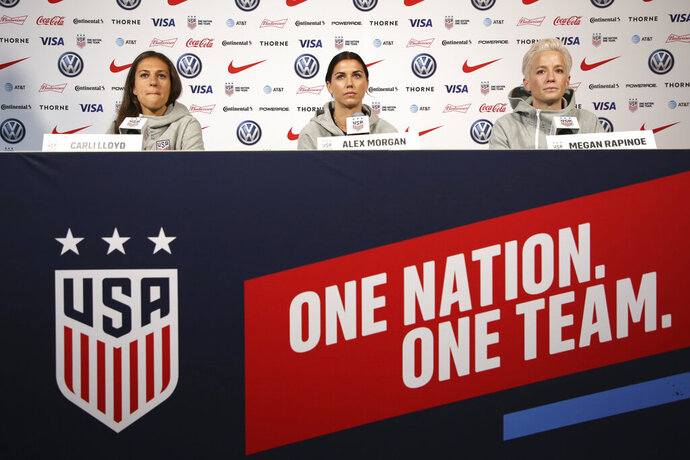 United States women's national soccer team members, from left, Carli Lloyd, Alex Morgan and Megan Rapinoe speak to reporters during a news conference in New York, Friday, May 24, 2019. (AP Photo/Seth Wenig)