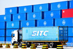 A container truck passes by stacks of COSCO containers on a dockyard of a port in Qingdao in eastern China's Shandong province Friday, June 4, 2021. China's exports surged nearly 28% in May while imports jumped 51% as demand rebounded in the U.S. and other markets where the pandemic is waning, though growth is leveling off after a stunning recovery from last year's slump. (Chinatopix via AP)