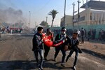 An injured protester is rushed to a hospital during clashes between security forces and anti-government protesters in central Baghdad, Iraq, Monday, Jan. 20, 2020. Security forces fired tear gas and live rounds on Monday wounding over a dozen protesters, medical and security officials said, in continuing violence as anti-government demonstrators make a push to revive their movement in Baghdad and the southern provinces. (AP Photo/Khalid Mohammed)