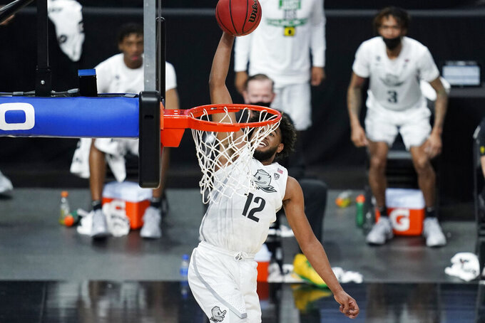 Oregon's LJ Figueroa (12) dunks against Arizona State during the second half of an NCAA college basketball game in the quarterfinal round of the Pac-12 men's tournament Thursday, March 11, 2021, in Las Vegas. (AP Photo/John Locher)