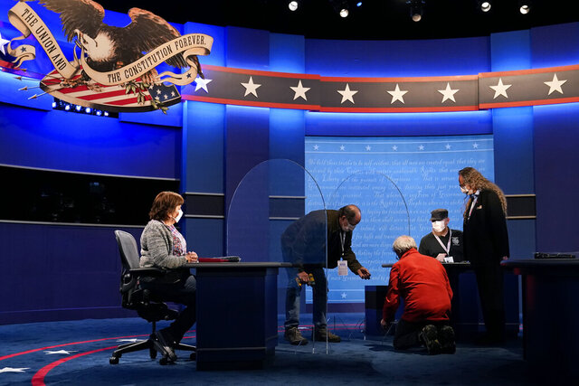Members of the production crew work on the stage near plexiglass barriers which will serve as a way to protect the spread of COVID-19 as preparations take place for the vice presidential debate at the University of Utah, Tuesday, Oct. 6, 2020, in Salt Lake City. The vice presidential debate between Vice President Mike Pence and Democratic vice presidential candidate Sen. Kamala Harris, D-Calif., is scheduled for Oct. 7. (AP Photo/Patrick Semansky)