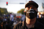 Raymond Curry attends a protest outside the Minneapolis 5th Police Precinct while wearing a protective mask that reads
