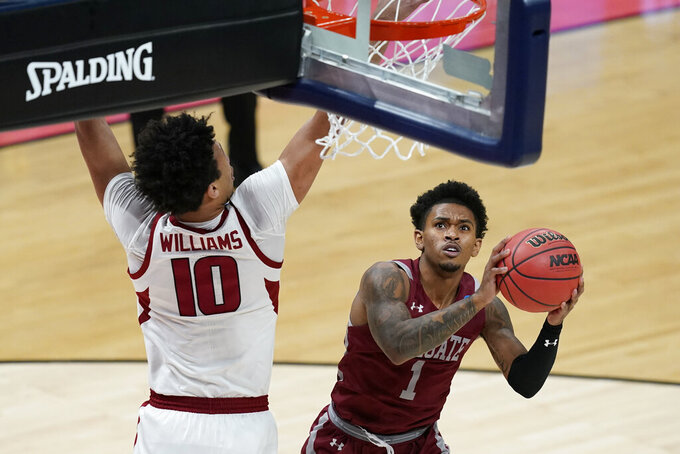 Colgate's Jordan Burns (1) puts up a shot against Arkansas' Jaylin Williams (10) during the first half of a first round game at Bankers Life Fieldhouse in the NCAA men's college basketball tournament, Friday, March 19, 2021, in Indianapolis. (AP Photo/Darron Cummings)