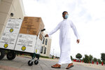 Saher Khan rolls boxes of treats to hand out during a drive-through Eid al-Fitr celebration outside a closed mosque in Plano, Texas, Sunday, May 24, 2020, during the coronavirus pandemic. (AP Photo/LM Otero)