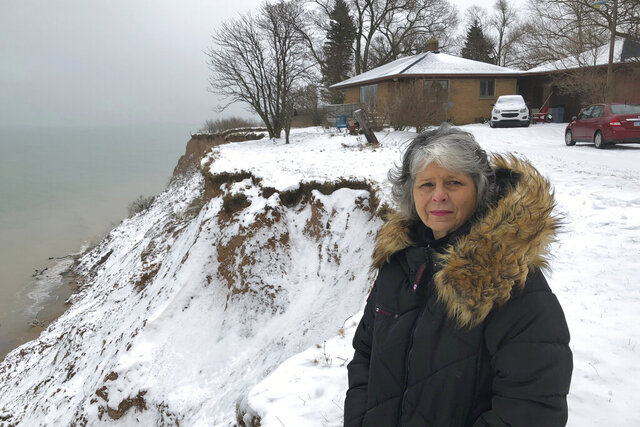 In this Jan. 14, 2020, photo, Rita Alton stands next to her house on the edge of a cliff overlooking Lake Michigan near Manistee, Mich. When her father built the 1,000-square-foot, brick bungalow in the early 1950s, more than acre of land lay between it and the drop-off overlooking the water. But erosion has accelerated dramatically as the lake approaches its highest levels in recorded history, hurling powerful waves into the mostly clay bluff. (AP Photo/John Flesher)