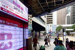 People wearing face masks walk in front of a bank's electronic board showing the Hong Kong share index at Hong Kong Stock Exchange Wednesday, Aug. 5, 2020. Major Asian stock markets declined Wednesday amid investor concern about U.S. stimulus spending and a trade agreement with Beijing. (AP Photo/Vincent Yu)