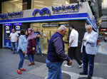 Lebanese clients wait outside a private bank for the opening after two weeks of closer, in Beirut, Lebanon, Friday, Nov. 1, 2019. Lebanon's private banks have reopened after a two-week closure because of anti-government protests. The reopening on Friday follows Prime Minister Saad Hariri's resignation this week, a key demand of the protesters. (AP Photo/Hussein Malla)
