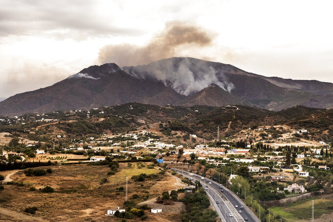 Smoke rises over smoking mountains, near the town of Jubrique, in Malaga province, Spain, Monday, Sept. 13, 2021. Firefighting crews in southern Spain are looking at the sky for much-needed rainfall they hope can help extinguish a stubborn mega-fire that has ravaged 7,400 hectares (18,300 acres) in five days and displaced just under 3,000 people from their homes. Authorities are describing the blaze in Sierra Bermeja, a mountain range in the Malaga province, as a sixth-generation fire of the extreme kind brought by the shifting climate on the planet. (AP Photo/Pedro Armestre)