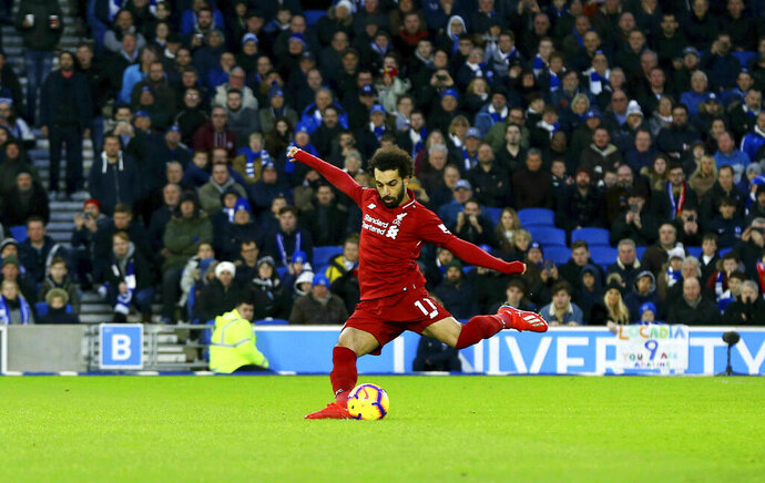 Liverpool's Mohamed Salah scores his side's first goal of the game from the penalty spot during the English Premier League soccer match between Brighton and Hove Albion and Liverpool F.C at the Vitality Stadium, Brighton England. Saturday, Jan. 12, 2019. (Gareth Fuller/PA via AP)