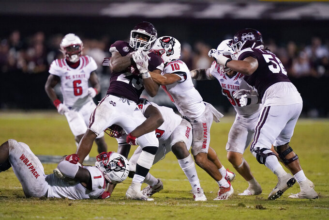 Mississippi State running back Dillon Johnson (23) is tackled by North Carolina State safety Tanner Ingle (10), linebacker Isaiah Moore (1) and another player during the second half of an NCAA college football game in Starkville, Miss., Saturday, Sept. 11, 2021. (AP Photo/Rogelio V. Solis)