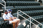 Tennis fans, Jeff Hartman, left, and Clay Gilbert, right, watch play at the start of the World Teamtennis tournament at an empty tennis arena at The Greenbrier Resort Sunday July 12, 2020, in White Sulphur Springs, W.Va. (AP Photo/Steve Helber)