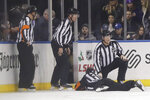 Officials check on referee Kendrick Nicholson (44) after Nicholson was hurt during the first period of an NHL hockey game between the New York Rangers and the Washington Capitals on Wednesday, Nov. 20, 2019, in New York. (AP Photo/Frank Franklin II)