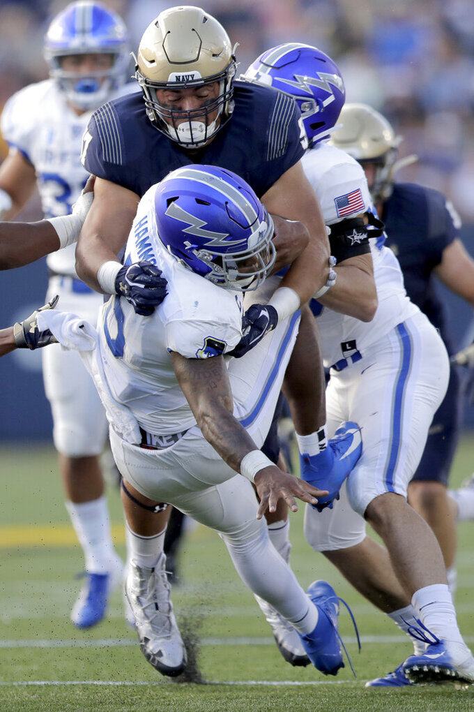 Air Force quarterback Donald Hammond III, bottom, is brought down by Navy defensive lineman Dave Tolentino during a quarterback keeper run in the first half of an NCAA college football game Saturday, Oct. 5, 2019, in Annapolis, Md. (AP Photo/Julio Cortez)