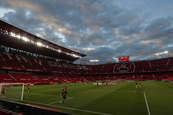 Sevilla and Betis players warm up before the start of their Spanish La Liga soccer match in Seville, Spain, Thursday, June 11, 2020. With virtual crowds, daily matches and lots of testing for the coronavirus, soccer is coming back to Spain. The Spanish league resumes this week more than three months after it was suspended because of the pandemic, becoming the second top league to restart in Europe. The Bundesliga was first. The Premier League and the Italian league should be next in the coming weeks. (AP Photo)