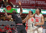 Temple center Ernest Aflakpui (24) loses the ball on a shot-attempt in front of Houston forward Breaon Brady (24) and Fabian White Jr. (35) during the first half of an NCAA college basketball game Thursday, Jan. 31, 2019, in Houston. (AP Photo/Michael Wyke)
