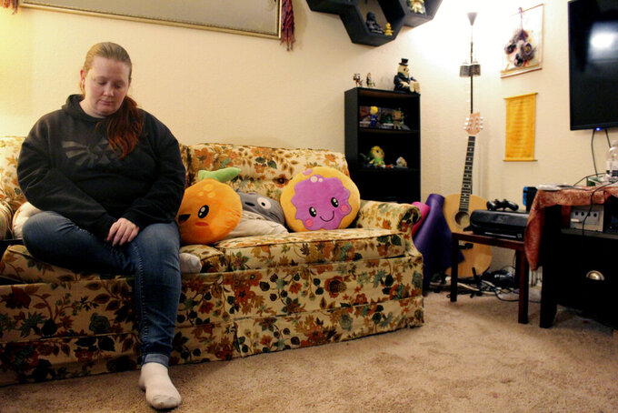 Taylor Wood sits on the couch in her Corvallis, Ore., apartment on Dec. 11, 2020. The Oregon native, who is 10 weeks pregnant, has not been able to get much sleep as she stresses about finances during the pandemic. (AP Photo/Sara Cline)