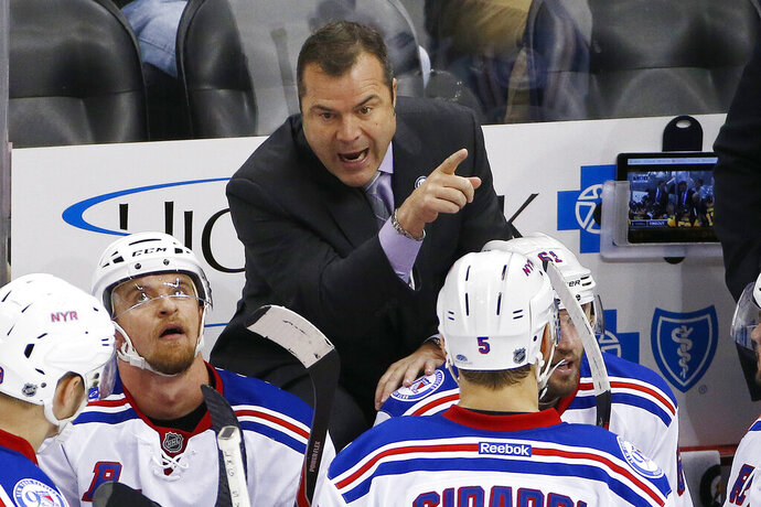 FILE - In this Nov. 2016, file photo, New York Rangers head coach Alain Vigneault, top, gives instructions in the third period of an NHL hockey game against the Pittsburgh Penguins in Pittsburgh. The Philadelphia Flyers have hired Vigneault as head coach. Vigneault has led the Rangers and Vancouver Canucks to the Stanley Cup final and takes over a Flyers team that missed the playoffs for the second time in three seasons. (AP Photo/Gene J. Puskar, File)