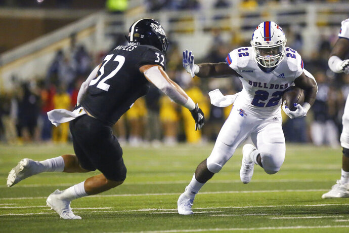 Louisiana Tech running back Israel Tucker (22) wards off a tackle from Southern Mississippi linebacker Hayes Maples (32) during the first half of an NCAA college football game in Hattiesburg, Miss., Saturday, Sept. 19, 2020. (Alyssa Newton/The Sun Herald, via AP)