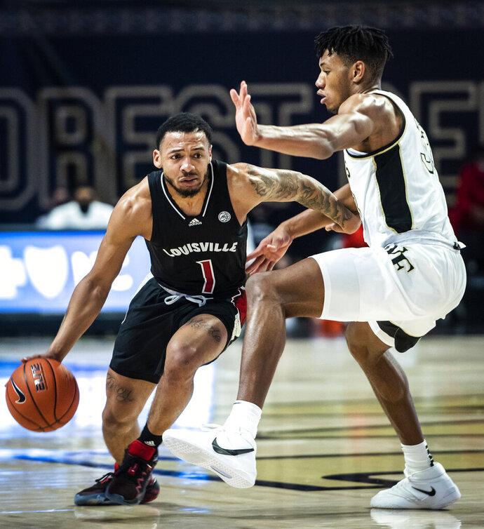 Louisville guard Carlik Jones (1) dribbles past Wake Forest forward Ody Oguama (33) during an NCAA college basketball game Wednesday, Jan. 13, 2021, in Winston-Salem, N.C. (Andrew Dye/The Winston-Salem Journal via AP, Pool)