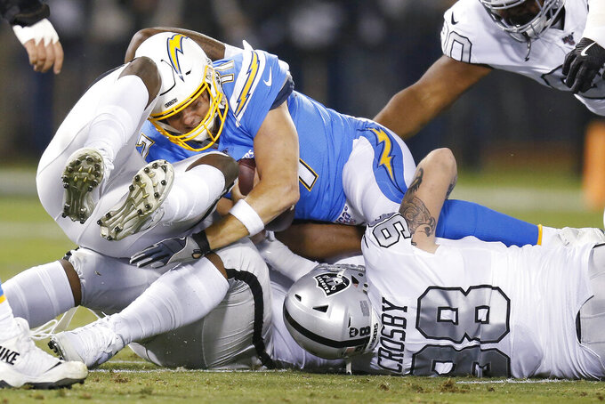 Los Angeles Chargers quarterback Philip Rivers, top, is sacked by Oakland Raiders defensive end Maxx Crosby, bottom right, and other Raiders during the first half of an NFL football game in Oakland, Calif., Thursday, Nov. 7, 2019. (AP Photo/D. Ross Cameron)