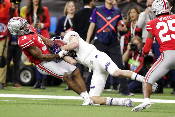 Northwestern wide receiver Charlie Fessler begins to fumble as he is tackled by Ohio State cornerback Damon Arnette (3) during the second half of the Big Ten championship NCAA college football game, Saturday, Dec. 1, 2018, in Indianapolis. After review, Fessler was ruled down before the fumble and Northwestern maintained in position of the ball. (AP Photo/Michael Conroy)