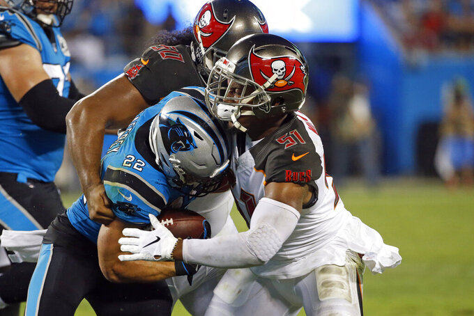 Carolina Panthers running back Christian McCaffrey (22) is tackled by Tampa Bay Buccaneers linebacker Kevin Minter (51) and defensive tackle Vita Vea (50) during the first half of an NFL football game in Charlotte, N.C., Thursday, Sept. 12, 2019. (AP Photo/Brian Blanco)