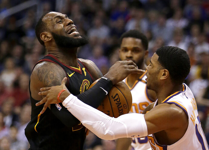 Cleveland Cavaliers forward LeBron James (23) gets fouled by Phoenix Suns guard Shaquille Harrison in the first half during an NBA basketball game, Tuesday, March 13, 2018, in Phoenix. (AP Photo/Rick Scuteri)