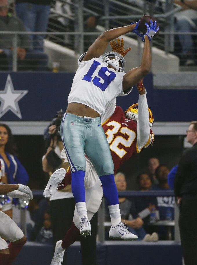 Dallas Cowboys wide receiver Amari Cooper (19) makes a catch over Washington Redskins cornerback Jimmy Moreland (32) during the first half of an NFL football game in Arlington, Texas, Sunday, Dec. 15, 2019. (AP Photo/Michael Ainsworth)