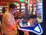 This June 23, 2021 photo shows a woman taking money out of her purse at a slot machine at Bally's casino in Atlantic City, N.J. Figures released on Sept. 16, 2021 show the Atlantic City casinos and the three racetracks that offer sports betting collectively won over $427 million in August, 31% more than they did in August 2020 as the casinos were just emerging from coronavirus-related closures. (AP Photo/Wayne Parry)