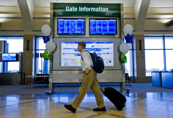 FILE - In this Nov. 13, 2011 file photo, a traveler walks past an information kiosk at Terminal C at John Wayne Airport in Santa Ana, Calif. The Southern California airport has cancelled all flights after a power outage left all its terminals in the dark. John Wayne Airport in Orange County diverted all arriving flights and cancelled departing flights after the outage hit at around Friday evening, Aug. 2, 2019. The airport's emergency power kicked in after about a half-hour but flights still remained grounded. (Michael Goulding/The Orange County Register via AP, File)