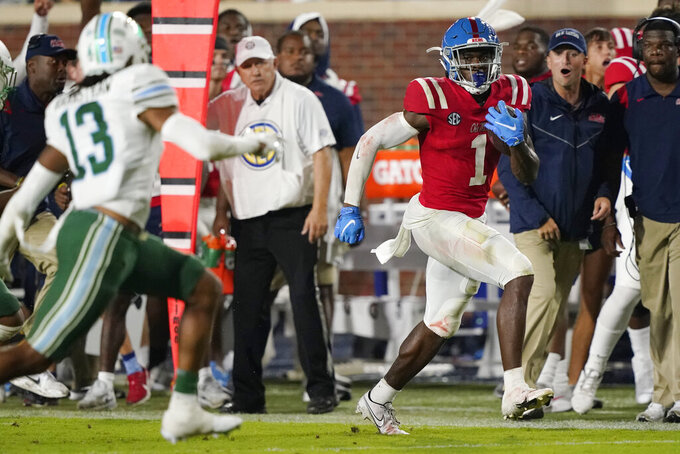 Mississippi wide receiver Jonathan Mingo (1) runs along the sideline after catching a pass as Tulane safety Derrion Rakestraw (13) pursues during the first half of an NCAA college football game Saturday, Sept. 18, 2021, in Oxford, Miss. (AP Photo/Rogelio V. Solis)