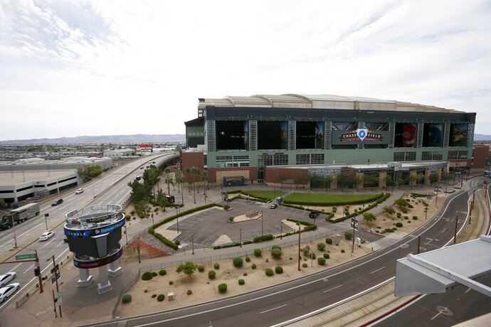 Traffic is extremely light in front of Chase Field, Thursday, March 26, 2020, in Phoenix. The Arizona Diamondbacks would have hosted the Atlanta Braves in their season-opening baseball game Thursday, but the start of the MLB regular season is indefinitely on hold because of the coronavirus pandemic. (AP Photo/Ross D. Franklin)